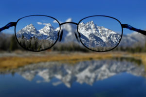Glasses with clear vision of Teton Mountains in background signifying power of clarity to improve productivity